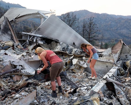 Elizabeth Barkley and her daughter Brooke sift through the ashes of their house.