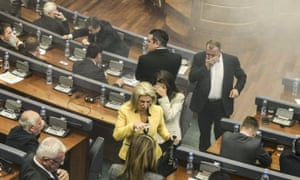 A white cloud of teargas ascends after being released by opposition legislators in Kosovo's parliament.