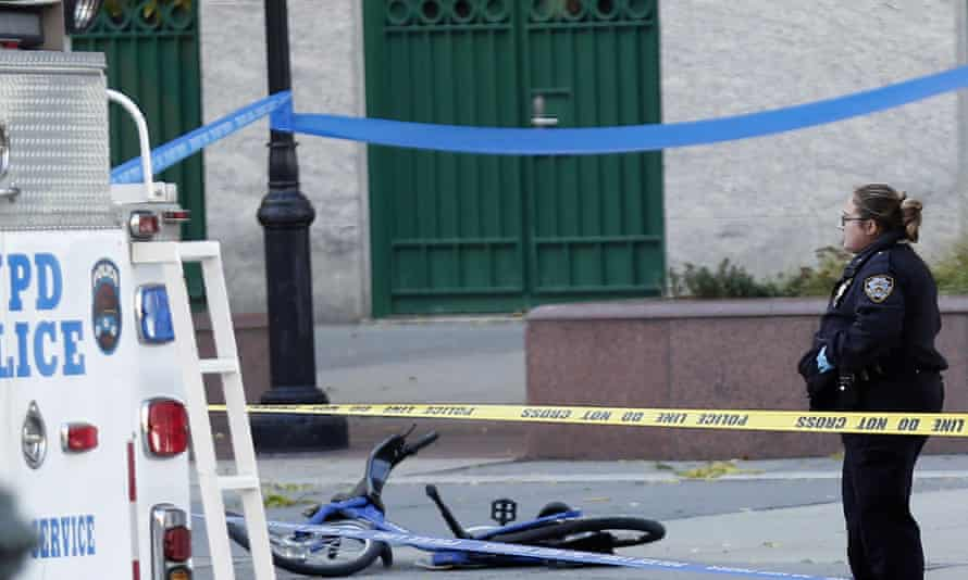 A NYPD officer stands near a mangled bike along a bike path Tuesday in New York.