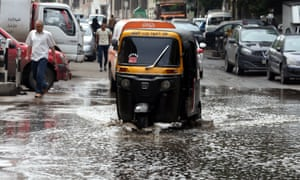A taxi drives through a flooded street in Cairo