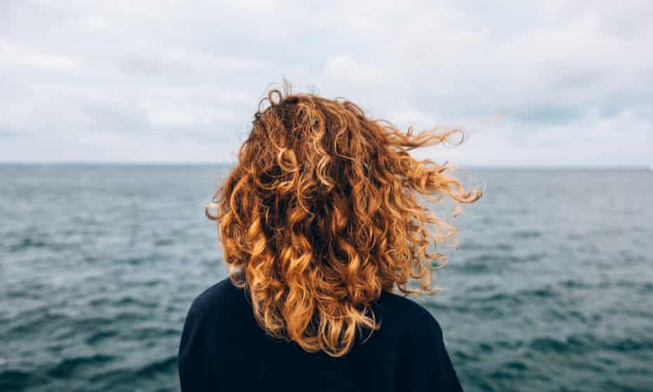 woman with red curly hair looks out to sea