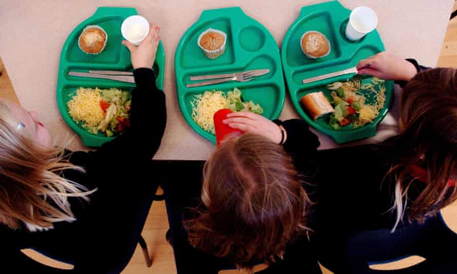 School pupils eat lunch out of trays