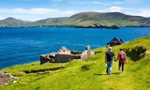 Visitors walk by the remains of a village on Great Blasket.