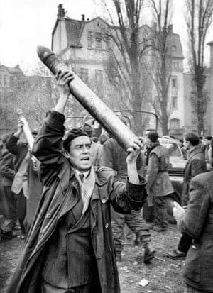 A fighter triumphantly holds up a looted Soviet tank shell, which arrived in a truck to be used in rebel tanks flying Hungarian flags