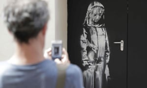 A man takes a photograph of an artwork by street artist Banksy in Paris on a side street to the Bataclan concert hall where a terrorist attack killed 90 people in November 2015.