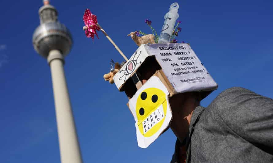 A man wears a box that reads: 'Do you need Mama Merkel? Papa Drosten? Grandpa Gates? Or are you still capable of independent thinking?' during a protest in Berlin against lockdown measures.