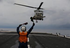 A sailor guides the landing of a Seahawk helicopter