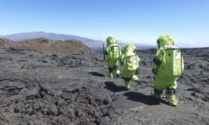 Crew members of Mission V, walk across lava next to the university's facility Hawaii Space Exploration Analog and Simulation (HI-SEAS).