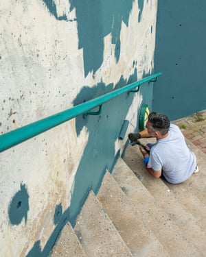 Remi Rough works on the mural.