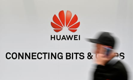 A man walks past a Huawei logo