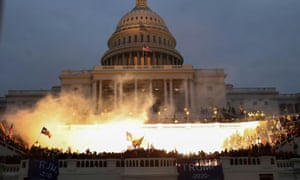 An explosion caused by a police munition is seen as supporters of Donald Trump storm the Capitol in Washington.