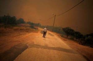 A man walks on the road as a wildfire approaches Pedreira.