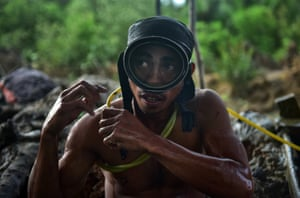 Anthony Balderosdasco, a young miner, prepares to dive under the mud
