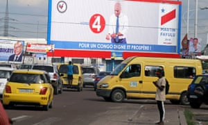 Taxis drive past a campaign poster for Martin Fayulu in Kinshasa.