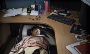 A Huawei employee rests in his cubicle in the research and development area at the Bantian campus in Shenzen, 12 April