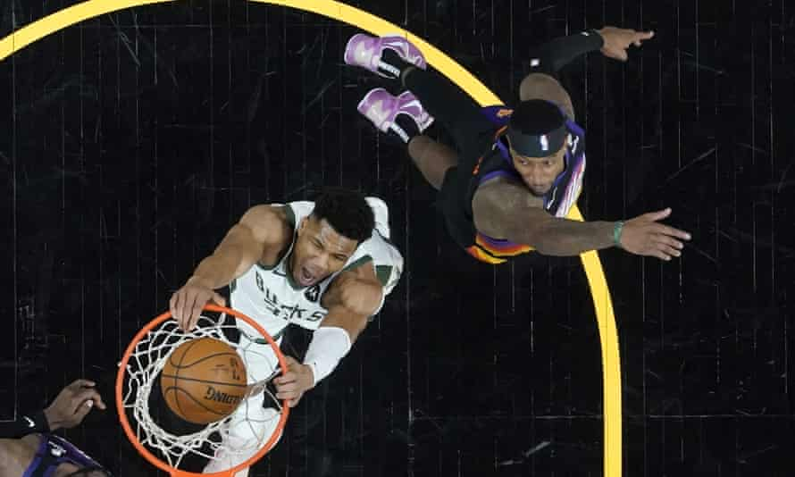 Giannis Antetokounmpo dunks as Phoenix Suns forward Torrey Craig, right, looks on during the first half of Game 1 of the NBA finals
