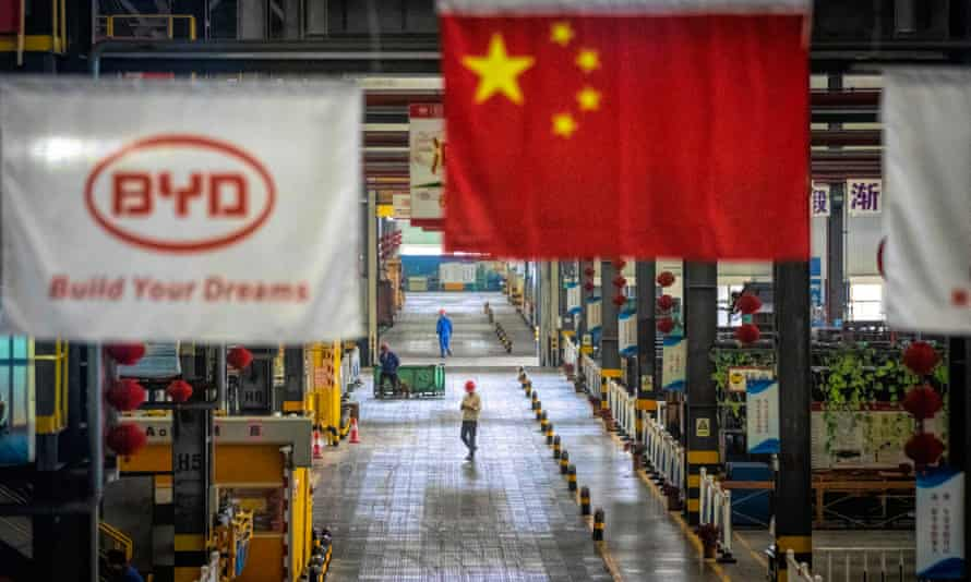 A Chinese flag hangs over the factory floor at Chinese carmaker BYD