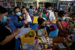 Mothers and their children wait for free vitamins and medicine at a local health centre in Manila.