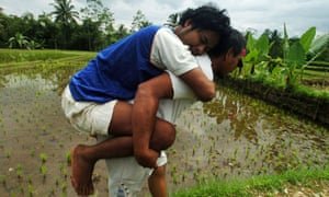 Villager in West Java, Indonesia, carries someone suffering from mental ill health.