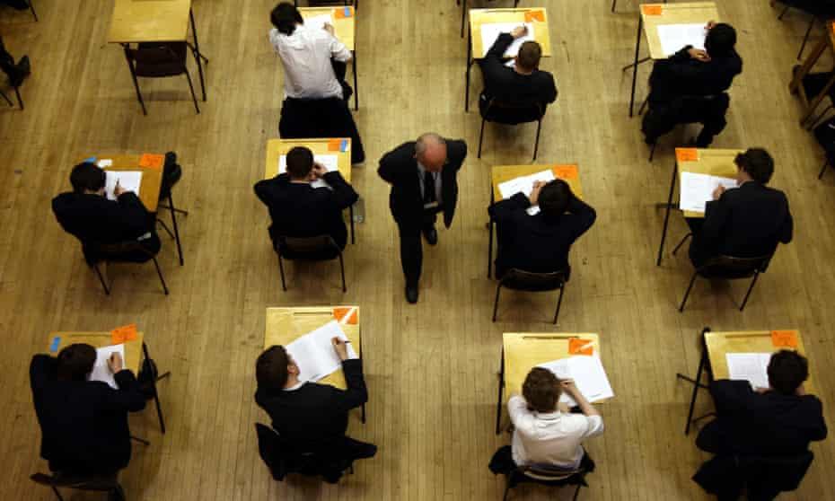 Students taking a GCSE exam as a teacher walks past.