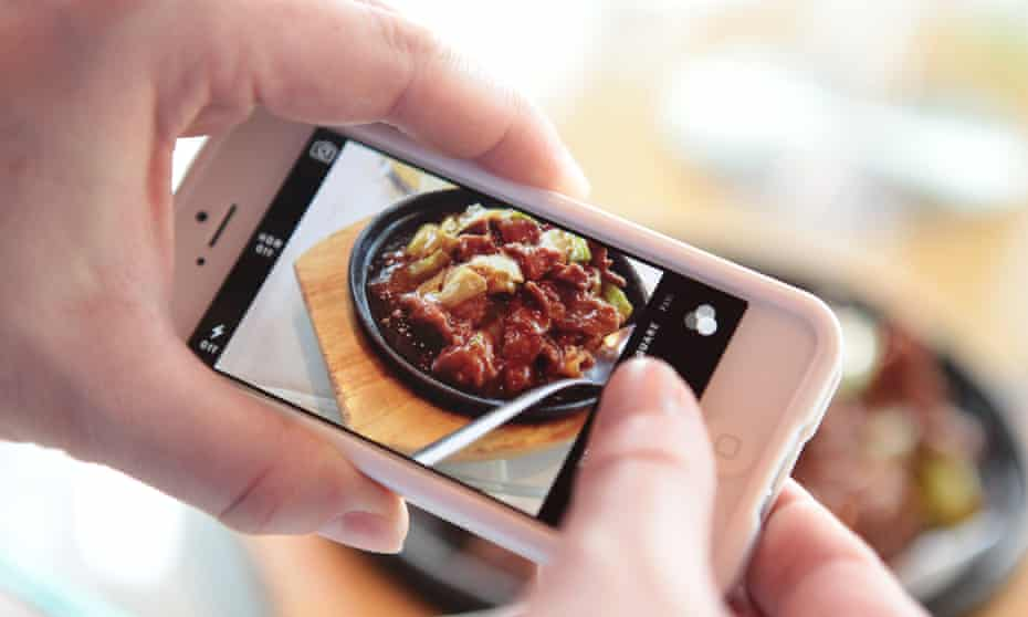 someone taking a picture of food on Instagram.