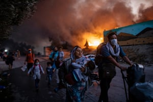 Refugees and migrants carrying their belongings flee a fire burning at the Moria camp on the northeastern Aegean island of Lesbos, Greece