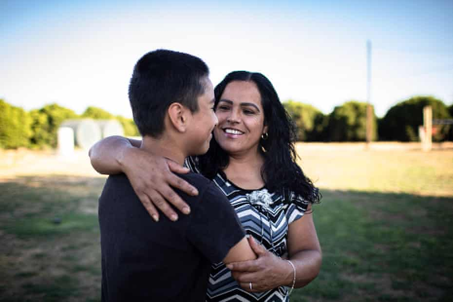 Fidelia Morales hugging her son Junior in their backyard that is surrounded by orange tress on all sides.