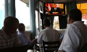 People listen as Puerto Rican governor Alejandro Garcia Padilla addresses the island's residents in a televised broadcast regarding the governments $72bn debt.