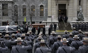 State troopers salute as a casket containing the body of Mario Cuomo is carried from church.