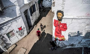 A man and a child walk past another man finishing a mural of Mohamed Salah in Cairo.