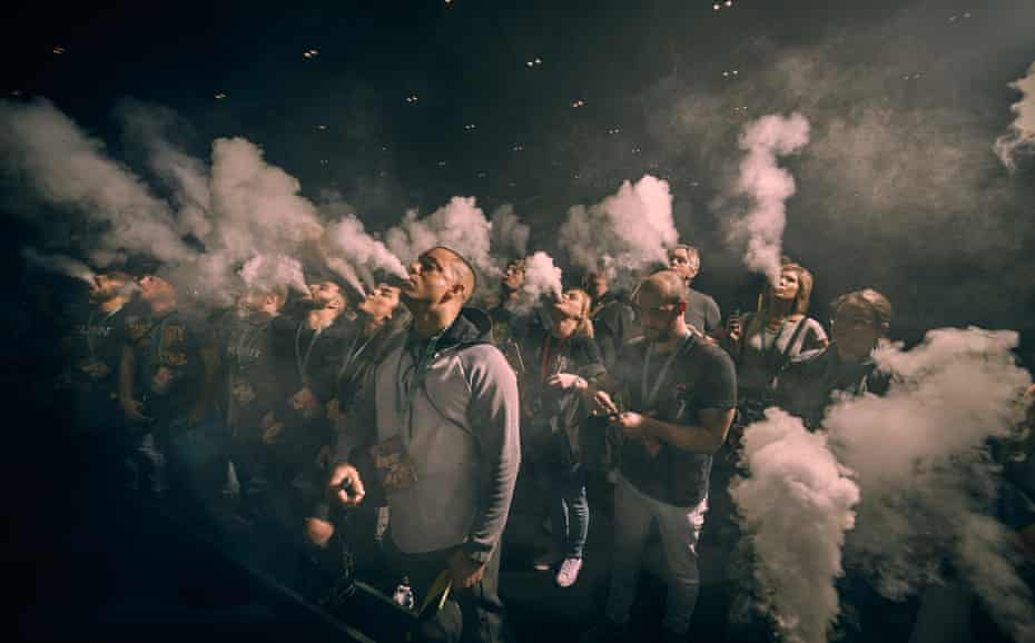 Participants exhale in unison at a mass vape at the trade fair Vape Jam in London, in April 2018