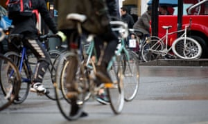 Central London cyclists wait at traffic signals by a 'ghost bike', left to mark the spot where a cyclist died.