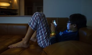 A boy looks at his smartphone