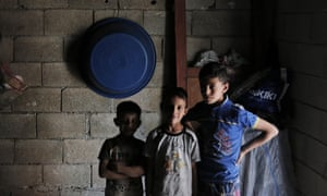 Syrian refugee children stand inside a commercial space that a family has rented to live in, in a neighborhood of the city of Gaziantep, Turkey