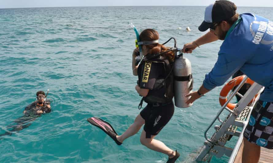 A scuba-diving tourist on the Ocean Freedom helped into the water by a crew member on the Great Barrier Reef.
