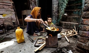 A woman cooks vegetables in palm oil outside her house in Delhi, India