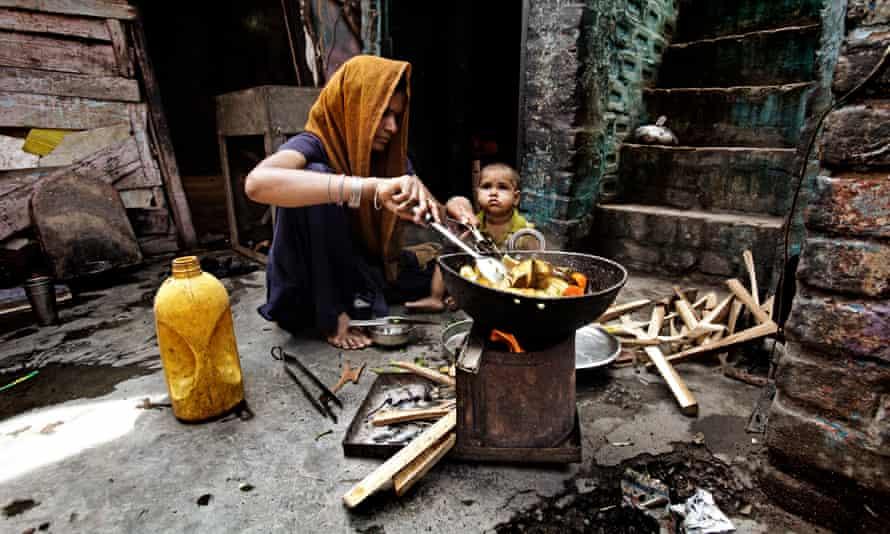 A woman cooks vegetables in palm oil outside her house in Delhi, India.