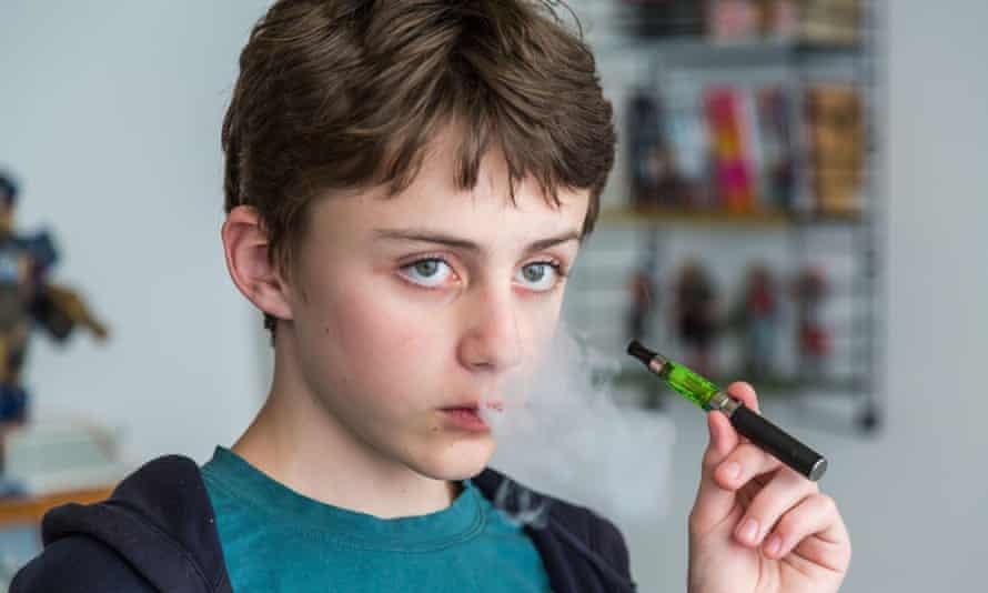 A teenager smoking an e-cigarette.