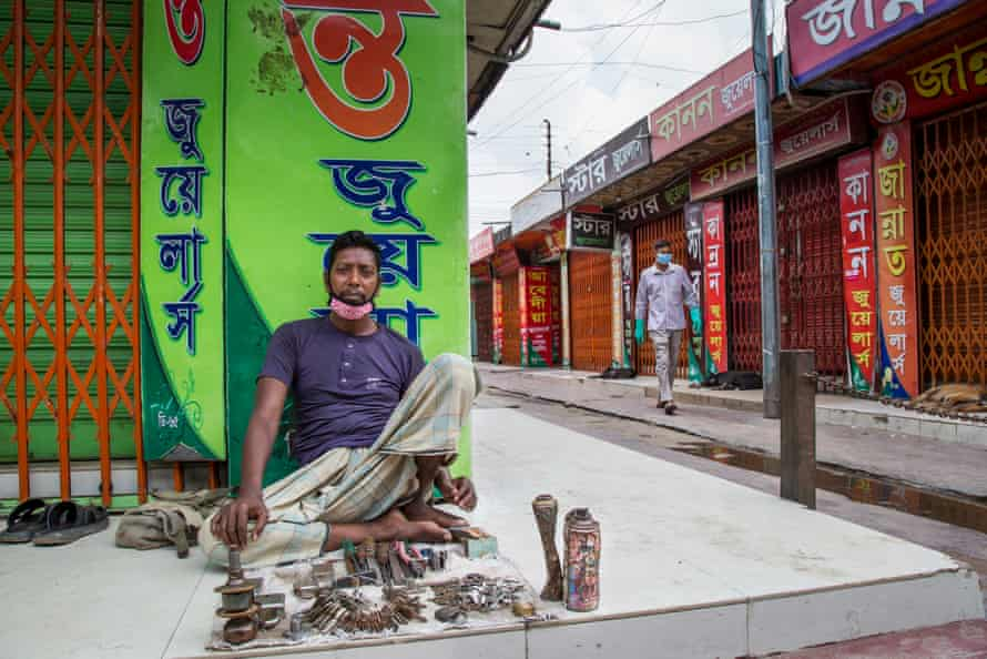 A keymaker on the pavement touts for business in an empty street