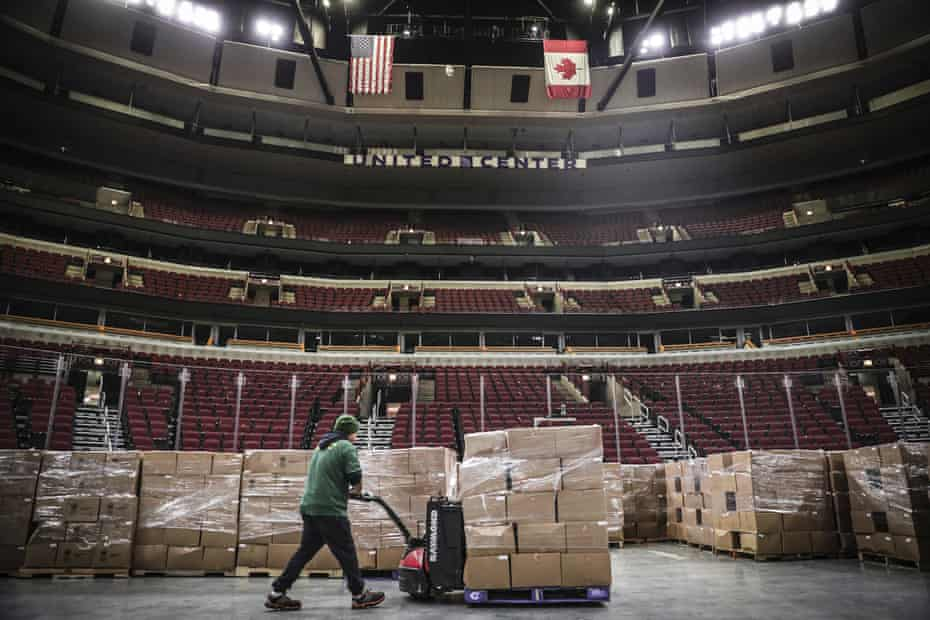 In this March 20, 2020 photo provided by the United Center, a worker moves food onto the floor of the United Center in Chicago. The Greater Chicago Food Depository, Chicago's food bank, will be utilizing the United Center as a satellite storage facility in response to the increased need for food during the coronavirus pandemic.