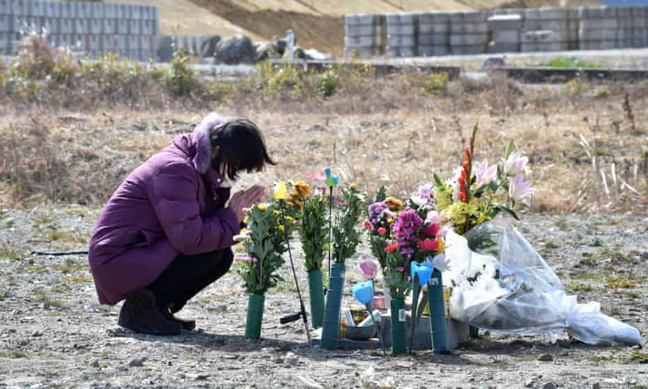 A woman prays for victims on the sixth anniversary of the 2011 quake-tsunami disaster in Namie, a no-entry zone in Fukushima prefecture.