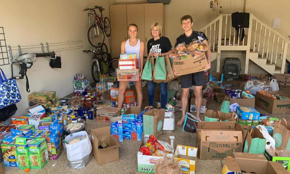 Katie Swan (left) with her mum, Nicki, and brother, Luke, putting together food parcels in their garage in Wichita, Kansas.