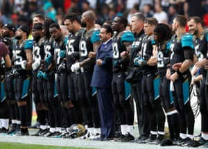 Jaguars owner Shahid Khan – who donated $1m to Donald Trump's inaugural committee – links arms with standing players as the anthem is played.