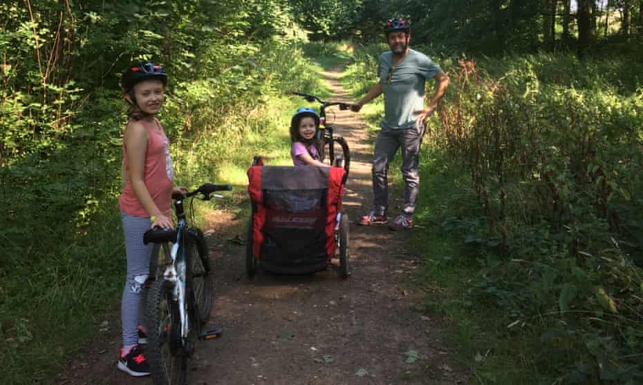 Chris Hall and his two young daughters with bikes on a woodland trail