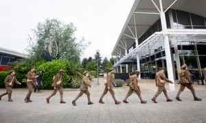 Soldiers walk through Milton Keynes after taking a train from Euston as part of an artwork.