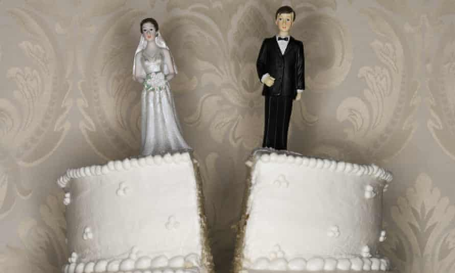 Wedding cake split down the middle, bride on one side, groom on the other