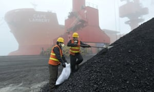 workers inspect piles of coal at a port in China