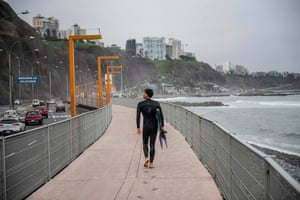 A surfer leaves his footprints on the pavement next to La Pampilla beach