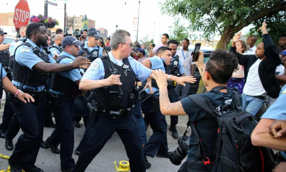 Police scuffle with an angry crowd at the scene of a police shooting in Chicago.