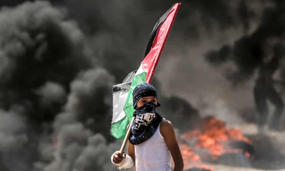 A Palestinian boy holding the national flag near the border between the Gaza Strip and Israel.